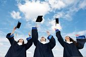 stock photo of graduation  - three graduate students tossing up hats over blue sky - JPG