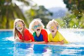 Kids Play In Swimming Pool. Children Learn To Swim In Outdoor Pool Of Tropical Resort During Family  poster
