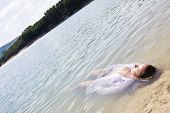 stock photo of braless  - Young woman floating in nature - JPG