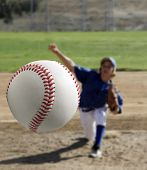 Youth baseball pitcher - person unrecognizable in background. Baseball focused in foreground