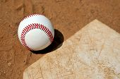 Symbols of a baseball season - ball on dirt infield next to home plate
