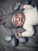Closeup portrait of a sweet newborn baby wearing gray knitted rabbit hat and sleeping on the gray bl poster
