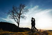 Silhouette Of A Couple In Love. Guy And Girl Hugging At Sunset. Couple Travels. Lovers In Nature. Ma poster