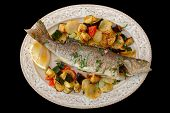 Fried sea bass with baked vegetables shot from above, Italian dish, isolated on black background poster