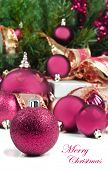 Pink christmas decorations under a christmas tree in low light with high contrast