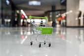 Little Shopping Trolley On Tile Floor Of Empty Shopping Centre. Concept Of Buying Things In Mall. To poster