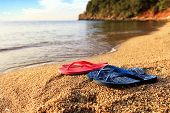 Beach Slippers Lie On A Stone Near The Transparent Sea poster