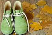 pair of green leather boots and yellow leaves on an old wooden floor