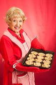 Sweet homemaker grandma holding a tray of fresh baked chocolate chip cookies.  Photographed in front
