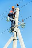 stock photo of lineman  - Electrician lineman repairman worker at climbing work on electric post power pole - JPG
