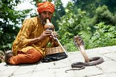 Indian Snake charmer adult man in turban playing on musical instrument before snake at a basket
