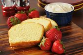 foto of pound cake  - Sliced pound cake fresh strawberries and whipped cream on a cutting board - JPG