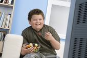 image of obesity children  - Smiling overweight boy eating bowl of fruit in front of television - JPG