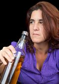 Drunk latin woman holding a whisky bottle (isolated on black)