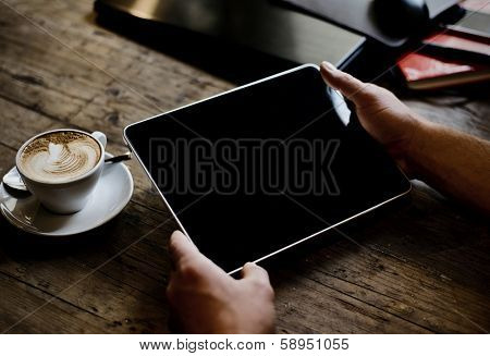 hands of a man holding blank tablet device over a wooden workspace table poster