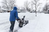 stock photo of blowers  - Man pushing a gas snow blower on the sidewalk - JPG