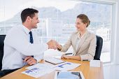 stock photo of half-dressed  - Smartly dressed young man and woman shaking hands in a business meeting at office desk - JPG