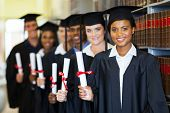 stock photo of laws-of-attraction  - group of happy graduates holding diploma in library - JPG