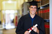 handsome male graduate wearing graduation gown in library