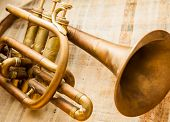stock photo of trumpets  - Old damaged brass trumpet photographed on papyrus - JPG