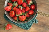 pic of over counter  - Bowl of freshly harvested ripe red strawberries waiting on a wooden kitchen counter to be made into jam over head view - JPG