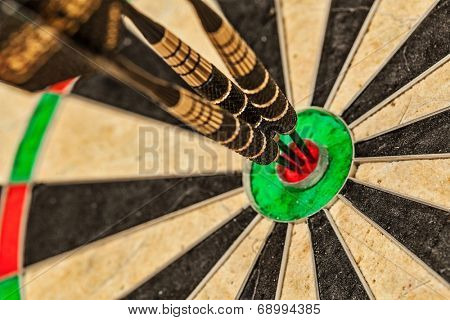 Success hitting target aim goal achievement concept background - three darts in bull's eye close up poster