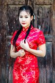 image of traditional attire  - Chinese girl in traditional Chinese cheongsam blessing