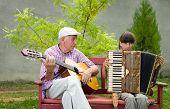 stock photo of grandpa  - Girl and grandpa playing musical instruments in garden - JPG