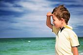 stock photo of azov  - boy looking away from his palm on the background of cloudy sky and sea horizontal - JPG