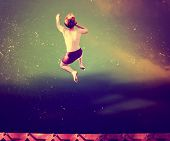 stock photo of gravity  -  a boy jumping of an old train trestle bridge into a river done with a retro vintage instagram filter  - JPG