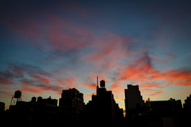 pic of nightfall  - Nearing nightfall twilight draws the contours of Chelsea rooftops and water towers under a dark blue sky and red clouds - JPG