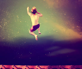 image of trestle bridge  -  a boy jumping of an old train trestle bridge into a river done with a retro vintage instagram filter  - JPG