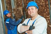 stock photo of millwright  - cheerful plasterer worker at a indoors wall insulation works - JPG