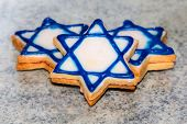 picture of star shape  - three biscuits in the shape of a Star of David white with blue edging lie on the surface the Jewish star