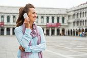 picture of piazza  - Portrait of happy young woman talking cell phone on piazza san marco in venice italy - JPG