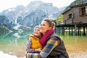 pic of south tyrol  - Happy mother and baby on lake braies in south tyrol italy looking into distance - JPG
