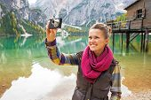 stock photo of south tyrol  - Smiling young woman taking photo on lake braies in south tyrol italy - JPG
