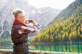 pic of south tyrol  - Smiling young woman taking photo on lake braies in south tyrol italy - JPG