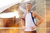 stock photo of jogger  - Portrait Of Happy Mature Male Jogger With Earphone Looking At Camera Outdoor - JPG