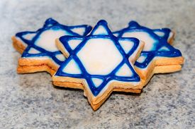 stock photo of star shape  - three biscuits in the shape of a Star of David white with blue edging lie on the surface the Jewish star  - JPG