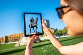 stock photo of albania  - Young woman tourist photographing with digital tablet Skanderbeg monument in Tirana - JPG
