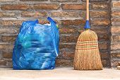 stock photo of broom  - Household Used Broom For Floor Dust Cleaning and Blue Plastic Garbage Bag Horizontal - JPG