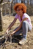 stock photo of spring-cleaning  - Caucasian woman spring cleaning the orchard gathering cut branches to throw them away - JPG
