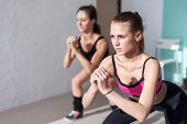 picture of squatting  - two girls doing squats together indoors training warm up at gym   - JPG