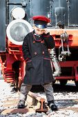 stock photo of nostalgic  - Nostalgic little child boy railroad conductor stand in front of a steam locomotive - JPG