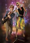 picture of rockabilly  - Rockabilly couple having fun playing the guitar and singing on a colorful background with glowing lights - JPG