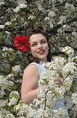 foto of dogwood  - beautiful retro pin up girl standing next to a blooming dogwood tree in the spring - JPG