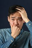 picture of disappointed  - Disappointed young Asian man looking sideways - JPG