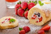 stock photo of mint leaf  - Sponge roll with strawberries and blueberries all fresh fruit sprinkled suger with mint leafes - JPG