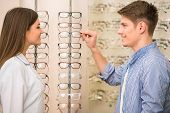 image of optical  - Optical store client man and professional specialist help to choose - JPG